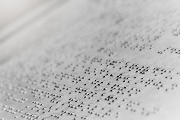 Close-up texto braille escrevendo sobre fundo de chapa de ferro