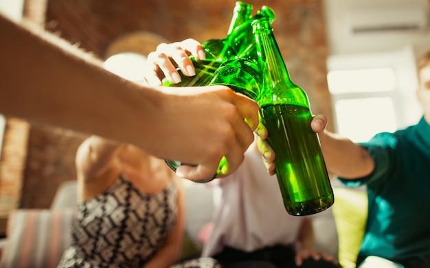 Close up tilintando. grupo de jovens amigos bebendo cerveja, se divertindo, rindo e comemorando juntos.