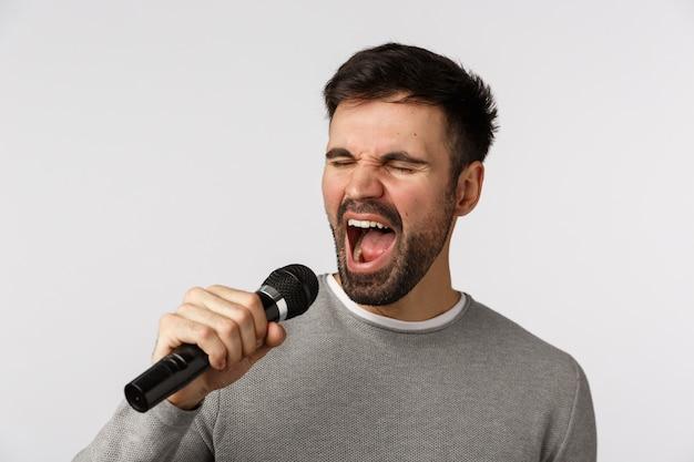 Close-up tiro alegre alegre homem despreocupado com barba, suéter cinza, cantando música otimista, segurando o microfone, levado com letras, assistir a noite de festa de karaokê, em pé