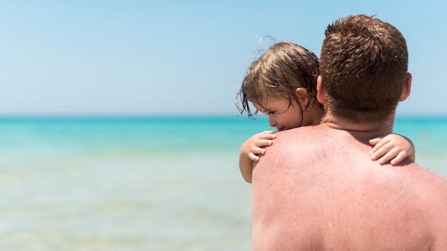 Close-up tiro com o pai segurando seu filho