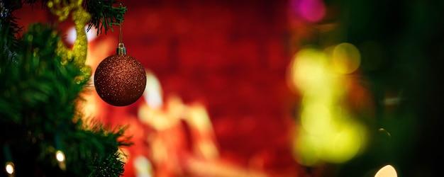 Close-up tiro da bola de esfera vermelha brilhante brilho brilhante pendurado decoração no galho de árvore de pinheiro de natal verde na frente do fundo desfocado no evento de noite de celebração tradicional festival de véspera de natal.