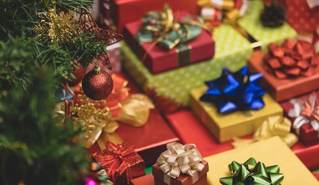 Close-up tiro da esfera vermelha brilhante decoração pendurada no galho de árvore do pinheiro de natal na frente da pilha de caixas de presente embrulhado véspera de natal com fitas coloridas e arcos no fundo desfocado.