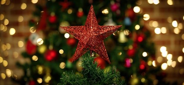 Close-up tiro da estrela de glitter vermelho brilhante cintilante com bonito papai noel decorando bonecos pendurados no topo do pinheiro de natal verde, celebrando o evento tradicional da noite festiva no fundo desfocado.