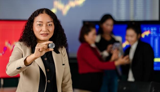Close-up tiro da moeda token virtual bitcoin criptomoeda na mão do investidor profissional comerciante feminino empresária bem-sucedida com borrão equipe de atendimento ao cliente no fundo.