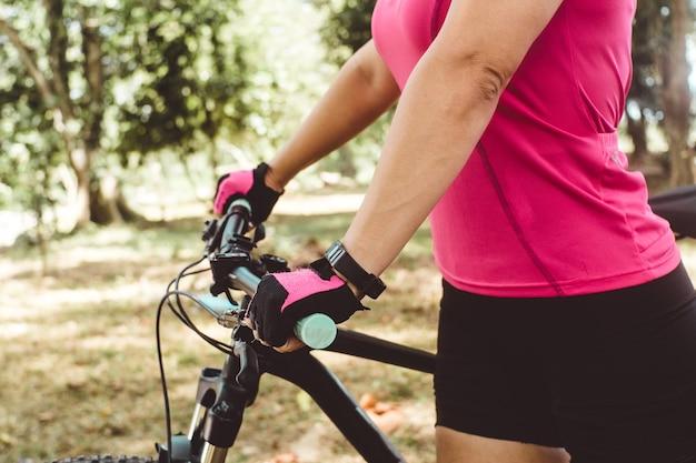 Close-up tiro das mãos de uma pessoa segurando uma bicicleta. conceito de esporte e ciclismo no ar ou na natureza.