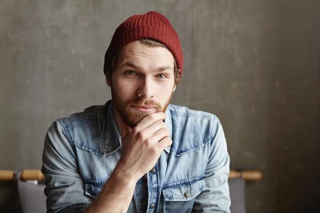 Close-up tiro de atraente jovem barbudo europeu bonito vestido com camisa jeans elegante e chapéu marrom sorrindo, tendo olhar pensativo, profundo e sábio, tocando sua barba