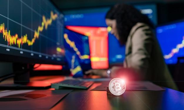 Close-up tiro de bitcoin criptomoeda com flare na frente feminino corretor asiático comerciante tipo de investidor no relatório de gráfico gráfico de estudo de computador portátil ao fazer transações on-line em fundo desfocado.