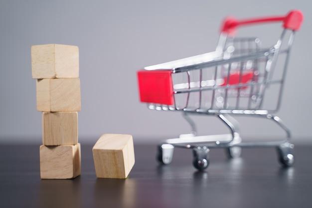 Close-up tiro de blocos de madeira vazios com carrinho de compras na mesa isolada em cinza.