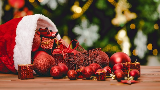 Close-up tiro de caixas de presente presentes de esfera estrela itens decorativos vermelhos derramando chapéu de natal na mesa de madeira na frente da bela totalmente decoração com flocos de gelo meias pinheiro no fundo desfocado.