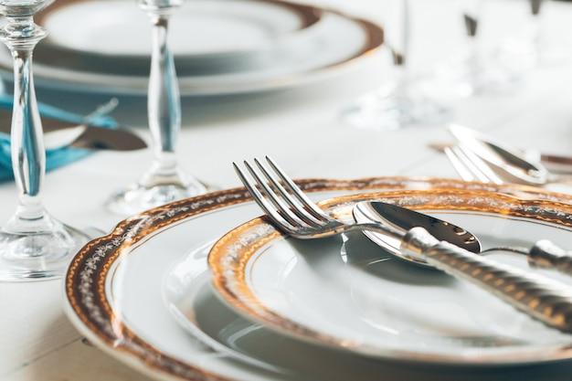 Close-up tiro de configuração de mesa para refeições requintadas com talheres e copos