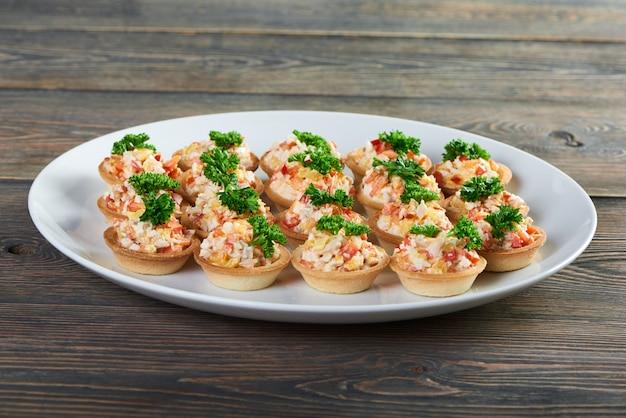 Close-up tiro de deliciosas tortinhas recheadas com salada decorada com verduras, servidas na placa de cerâmica branca na mesa de madeira na saborosa comida de aperitivo de menu do restaurante local.