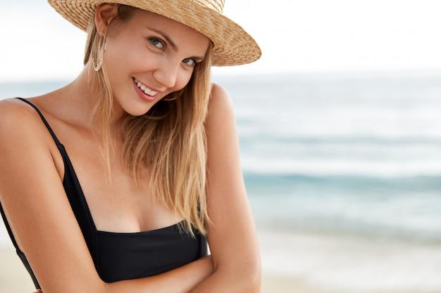 Close-up tiro de feliz jovem modelo feminino usa biquíni preto e chapéu de verão, tem uma expressão positiva, satisfeito com a caminhada ao ar livre pela costa do oceano, tem descanso e um bom resort nos trópicos.