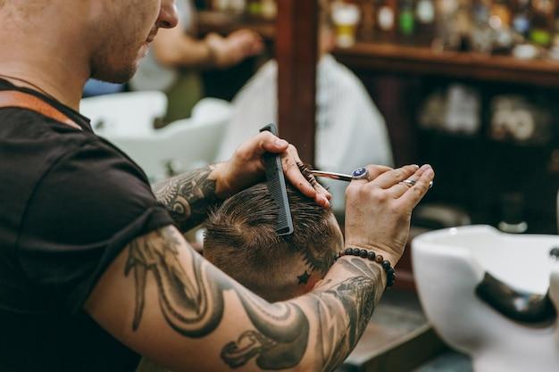 Close-up tiro de homem cortando o cabelo da moda na barbearia. o cabeleireiro masculino em tatuagens atendendo o cliente.