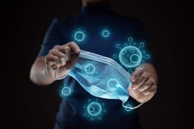 Close-up tiro de mãos segurando uma máscara protetora com efeito de holograma de vetor de vírus.