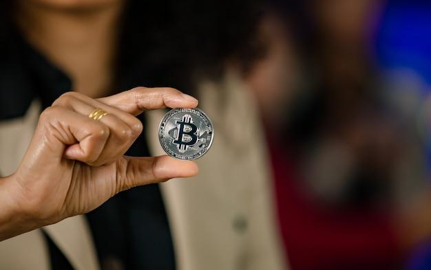 Close-up tiro de moeda virtual token bitcoin bitcoin prata na mão do investidor profissional profissional empresária bem-sucedida com espaço de cópia no fundo desfocado.
