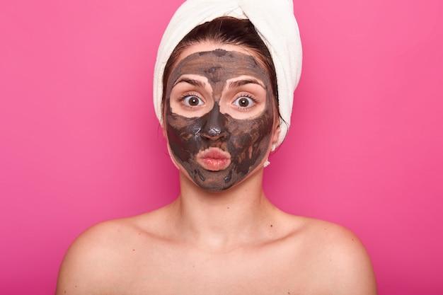 Close-up tiro de mulher bonita, tem máscara de chocolate no rosto, mantém os olhos bem abertos e lábios arredondados, posa com corpo nu, tem uma toalha branca na cabeça, tendo o resto no salão spa, isolado na parede rosa.
