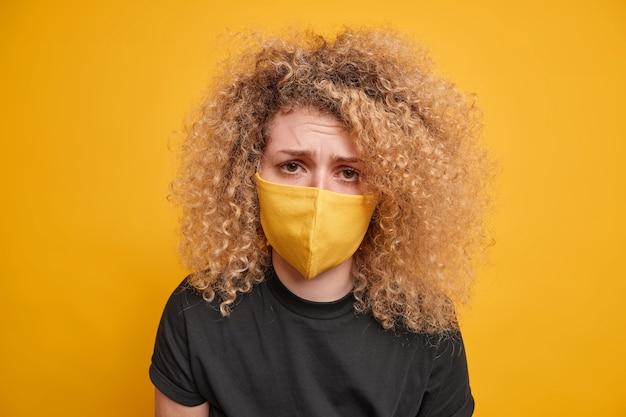 Close-up tiro de mulher de cabelo encaracolado parece, infelizmente, usa máscara protetora, sendo farto de restrições de bloqueio usa camiseta preta isolada sobre a parede amarela. pandemia do coronavírus