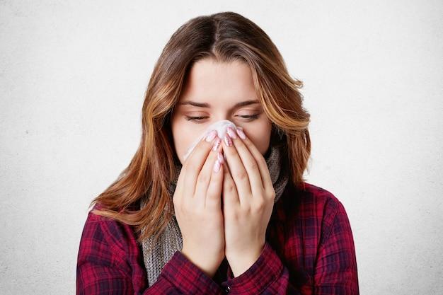 Close-up tiro de mulher doente pegou resfriado, sente-se doente, espirra em tecido de papel, tem coriza