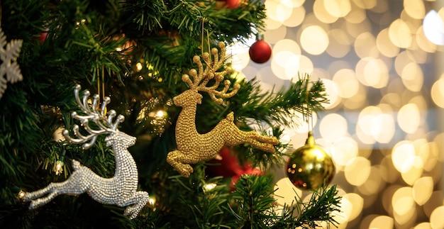 Close-up tiro de ouro e prata brilhante decoração véspera de natal renas pulando modelo pendurado decoração em galho de árvore de pinho de natal verde com bolas de esfera e flocos de gelo no fundo desfocado bokeh.