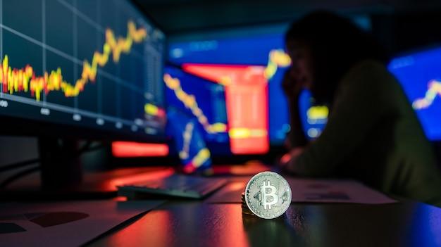 Close-up tiro de token virtual de criptomoeda bitcoin prata na mesa com chateado infeliz falha comerciante investidor olhando gráfico gráfico perda de valor na tela do monitor do computador em um fundo de sombra borrada.