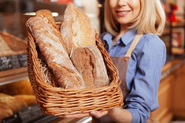 Close-up tiro de uma cesta cheia de deliciosos pães recém-assados nas mãos da alegre padeira