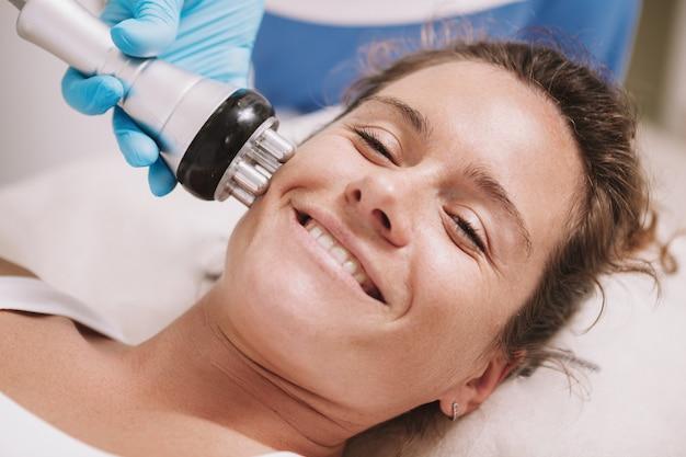 Close-up tiro de uma mulher madura feliz sorrindo, desfrutando de tratamento facial de rf-lifting na clínica de beleza