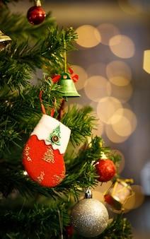 Close-up tiro de vermelho e branco decoração de véspera de natal meia decoração pendurada decoração em galho de árvore de pinho de natal verde com bola de esfera brilhante vara e sino na frente turva fundo dourado bokeh baixa luz.