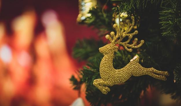 Close-up tiro do modelo de rena de decoração de véspera de natal brilhante pendurado decoração em galho de árvore de pinho de natal verde com bolas de esfera e outras coisas ornamentais na frente turva fundo de bokeh luz.