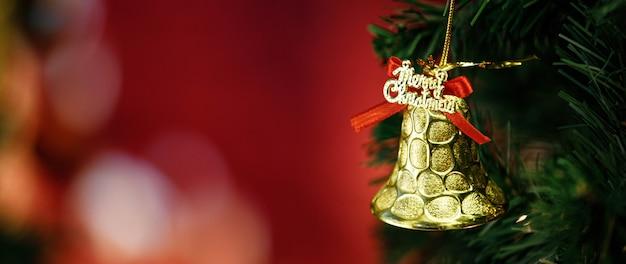 Close-up tiro do sino de brilho dourado brilhante com fita vermelha decoração pendurada no galho de árvore de pinheiro de natal verde na frente do fundo desfocado na noite de celebração tradicional do festival de véspera de natal.