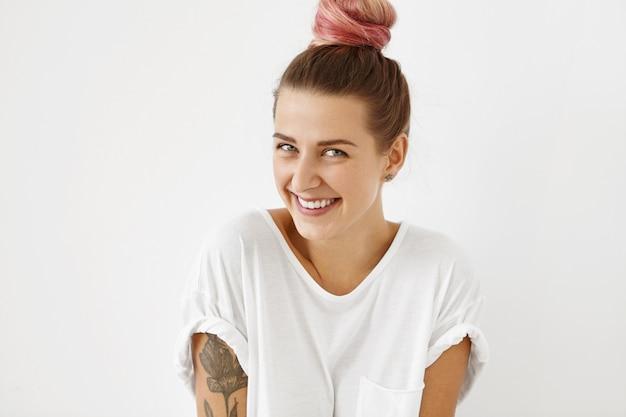 Close-up tiro indoor de atraente encantadora jovem mulher branca tatuada com misteriosos olhos azuis com cabelo rosa amarrado em nó