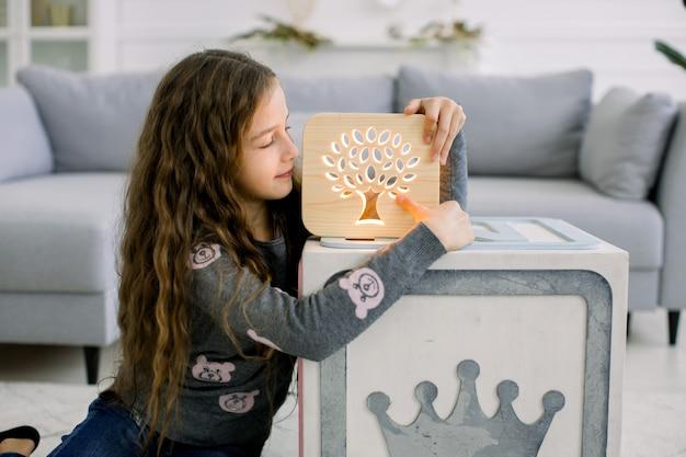 Close-up tiro interno de uma adorável menina criança, sentado na luz da sala de estar em casa e brincando com a lâmpada noturna de madeira feita à mão com bela imagem de árvore recortada.
