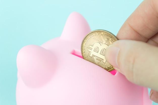 Close-up tiro mão colocando bitcoin ouro no cofrinho rosa. investindo economias em bitcoin.