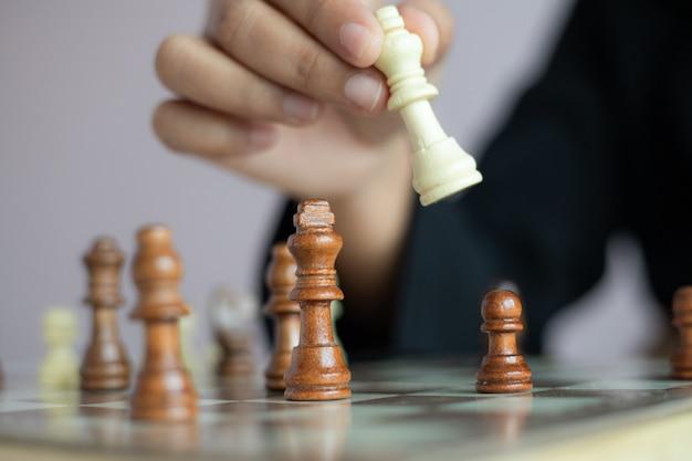 Close-up tiro mão de mulher de negócios jogando o tabuleiro de xadrez para vencer, matando o rei da metáfora do adversário vencedor da competição de negócios e perdedor selecione foco profundidade de campo