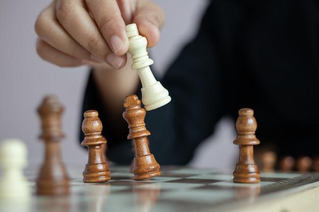Close-up tiro mão de mulher de negócios, jogando o tabuleiro de xadrez
