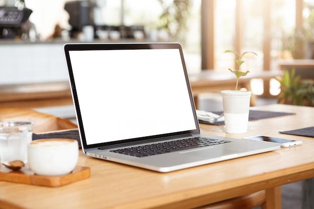 Close-up tiro minimalista do laptop genérico e acessórios de trabalho, descansando na mesa de madeira