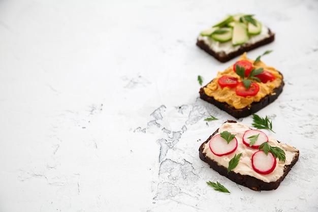Close-up torradas vegetarianas de pão de centeio com queijo cottage, homus, abacate, rabanete e tomate, cópia-espaço