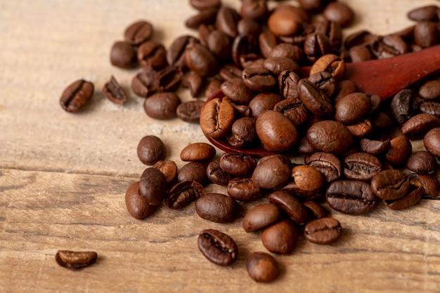 Close-up torrado grãos de café com uma colher