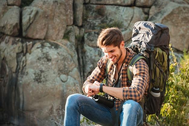 Close-up turista homem sentado na rocha perto do cânion