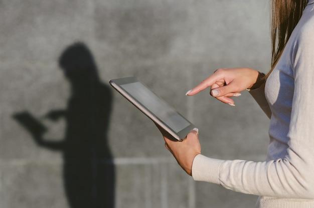 Close-up, um dedo na frente da tela do tablet, nas mãos de uma mulher de negócios. contra o fundo de uma parede de concreto cinza, uma silhueta permanece com uma sombra clara.