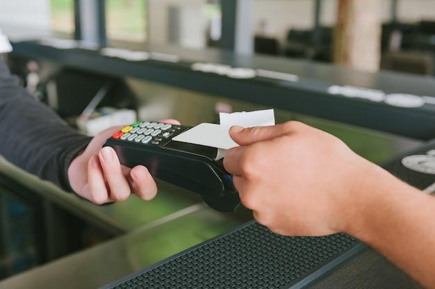 Close-up um homem está pagando com cartão de crédito no terminal.