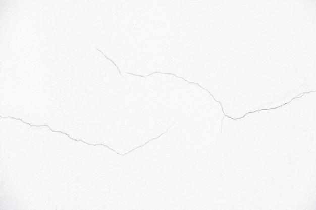 Close-up um pouco de rachadura de parede branca para textura de fundo decorativo