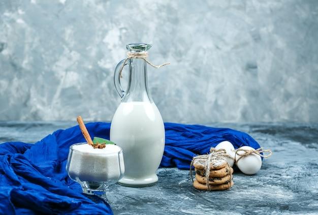 Close-up uma jarra de leite com lenço azul, gotas de chocolate e biscoitos brancos e uma tigela de vidro de iogurte na superfície de mármore azul escuro e cinza. horizontal