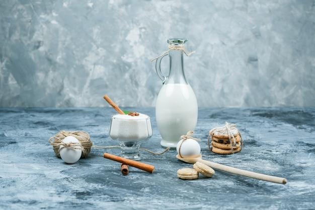 Close-up uma jarra de leite e uma tigela de vidro de iogurte com biscoitos, ovos, clew e canela na superfície de mármore azul escuro e cinza. horizontal