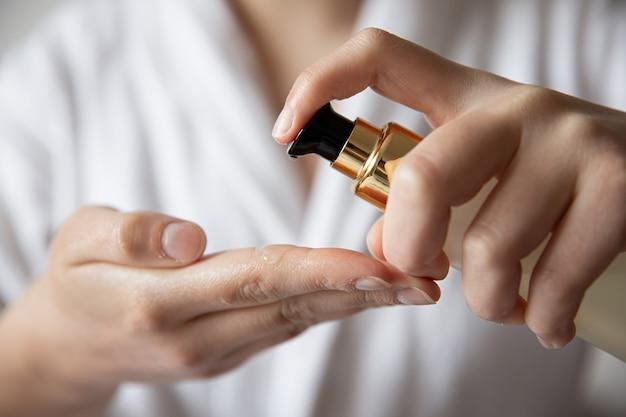 Close-up, uma mulher com uma túnica branca pressiona o distribuidor de produtos de beleza, fundo desfocado.