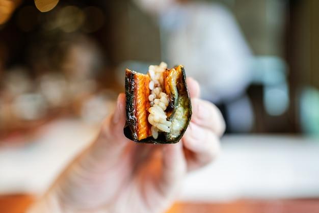 Close-up unagi (enguia grelhada japonesa) rolo de mão com algas grelhadas crocantes e arroz de sushi na mão.