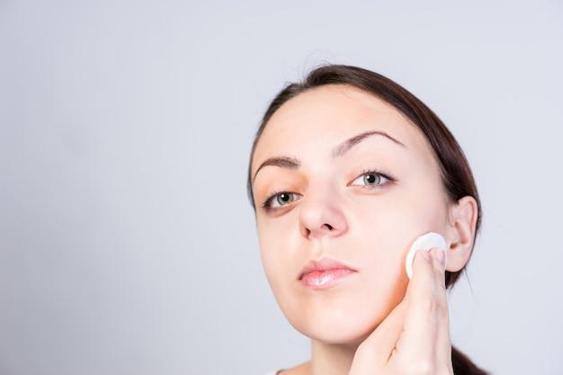 Close-up vaidosa jovem aplicando adstringente para limpar o rosto usando algodão, enquanto olha para a câmera. isolado em fundo cinza.