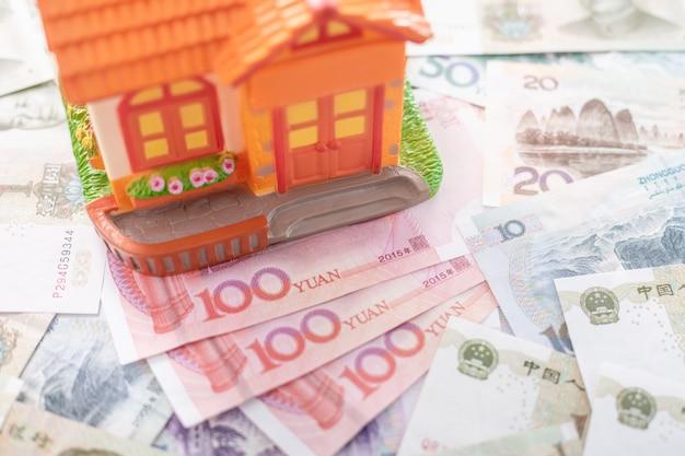 Close up várias notas de moeda chinesa yuan (cny ou rmb) e modelo de casa