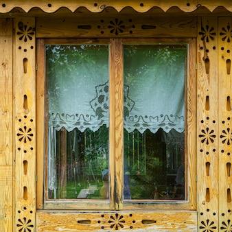 Close-up velha janela bonita com persianas de madeira esculpida artificialmente de pinheiro em uma casa de madeira