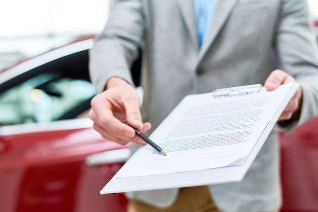 Close-up vendedor de carros, entrega de contrato para o cliente