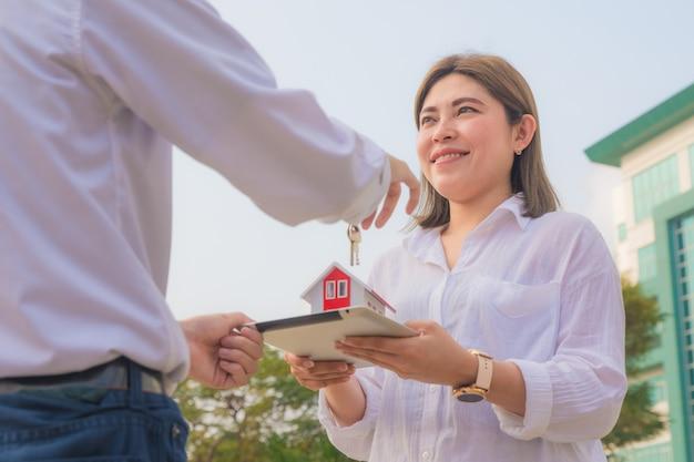 Close-up vendedor segurando a chave de casa para o conceito de aluguel de imóveis de venda comercial